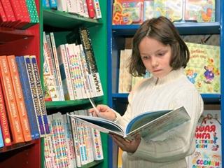 Девочка выбирает книгу для обучения