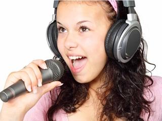 Девочка в наушниках поет песню