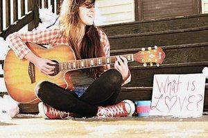 Девушка поет песню и играет на гитаре
